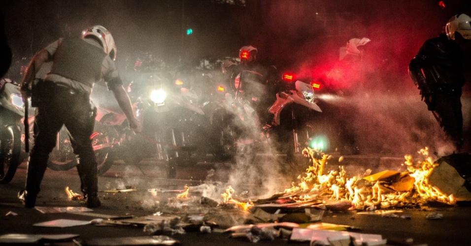 11.jun.2013 - Policiais tentam, com os pés e cassetetes, apagar fogo colocado por manifestantes em lixo espalhado na avenida Paulista, região central de São Paulo