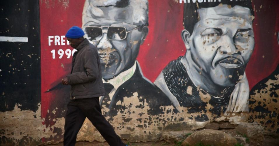 12.jun.2013 - Homem passa em frente a mural com rosto do ex-presidente da África do Sul Nelson Mandela, em Soweto. O líder do fim do apartheid está hospitalizado há cinco dias e respondendo melhor ao tratamento, informou nesta quarta-feira (12) o presidente da África do Sul, Jacob Zuma