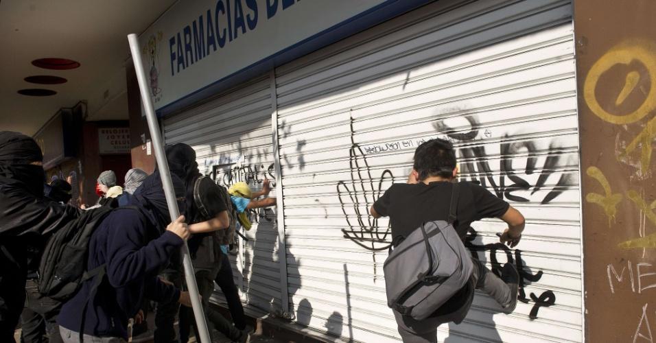 13.jun.2013 - Confrontos entre pessoas encapuzadas e a polícia foram registrados nesta quinta-feira no centro de Santiago, em uma nova marcha de estudantes que pedem reformas no sistema de ensino do país. Também foram registrados saques e depredação de patrimônio público. A polícia não informou ainda o número total de pessoas detidas, mas a imprensa local fala em dezenas