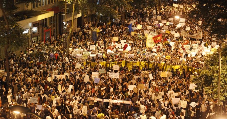 """17.jun.2013 - Manifestantes protestam no centro do Rio de Janeiro, nesta segunda-feira (17), contra o reajuste da tarifa de ônibus na cidade e os gastos com a Copa do Mundo. A manifestação teve início às 17h, com saída da Candelária rumo à avenida Rio Branco. Manifestantes organizam uma vaia coletiva para a presidente Dilma Rousseff. """"Essa vaia vai ecoar no Brasil inteiro. A gente não vai parar enquanto o aumentor não for suspenso. Queremos um transporte de qualidade"""", afirmou a estudante Priscilla Guedes, que integra a organização do ato simbólico"""