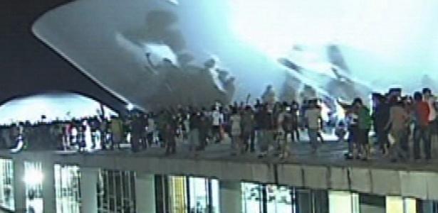 """17.jun.2013 - Manifestantes sobem as cúpulas do Congresso Nacional durante protesto na noite desta segunda-feira. Após serem contidos por um cordão de isolamento da PM, dezenas de manifestantes conseguiram furar o bloqueio e invadiram a área externa do Congresso Nacional, em Brasília, aos gritos de """"a-ha, u-hu, o Congresso é nosso"""""""