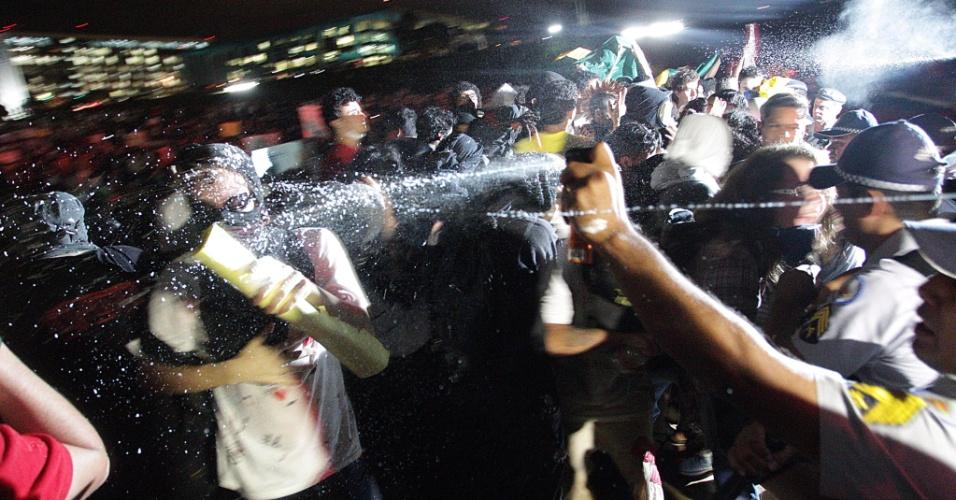 17.jun.2013 - Policial usa spray para conter manifestante durante protesto que segue pela Esplanada dos Ministérios até o Congresso Nacional em Brasília, na noite desta segunda-feira. Alguns manifestantes tentam invadir o Congresso Nacional subindo pelas rampas