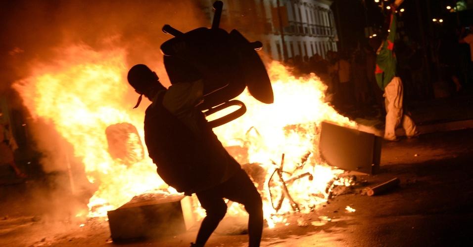 Manifestante atira cadeira em fogueira feita em rua durante protestos no centro do Rio de Janeiro