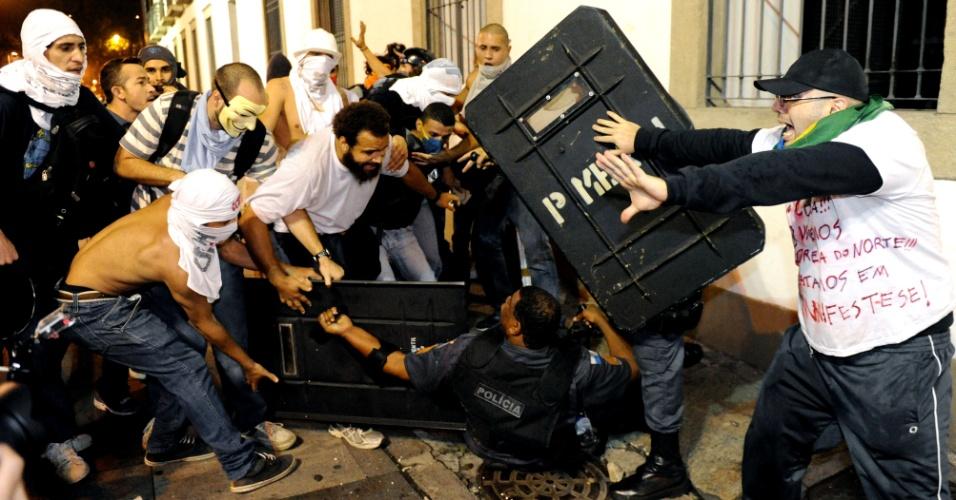 17.jun.2013 - Policial cai no chão durante confronto com grupo de manifestantes em protesto pelas ruas do Rio de Janeiro, nesta segunda-feira (17)