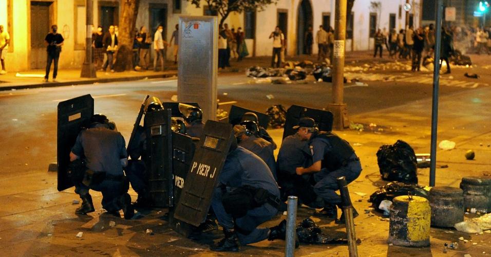 17.jun.2013 - Policiais da tropa de choque se protegem de grupo de manifestantes diante da Alerj (Assembleia Legislativa do Rio de Janeiro). Cerca de 100 mil foram à Cinelândia, no centro do Rio, e marcharam em direção à Alerj em protesto contra o aumento nas tarifas de ônibus