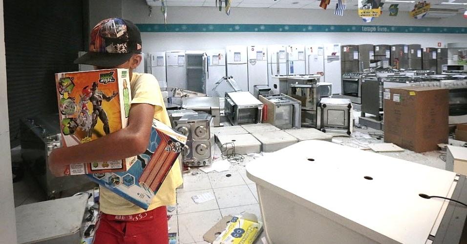 18.jun.2013 - Garoto leva brinquedos de loja saqueada durante o sexto protesto contra o aumento das tarifas do transporte público no centro de São Paulo, na noite de terça-feira (19). Com o arrombamento das portas, as lojas foram alvos de saques de eletrônicos, eletrodomésticos e brinquedos