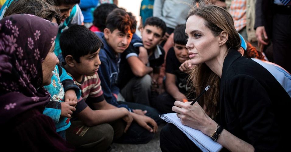 19.jun.2013 - Angelina Jolie conversa com crianças sírias que vivem em um campo de refugiados na fronteira da Jordânia. A viagem da atriz, que é embaixadora da ONU (Organização das Nações Unidas), coincide com o Dia Mundial do Refugiado, celebrado nesta quinta-feira (20)