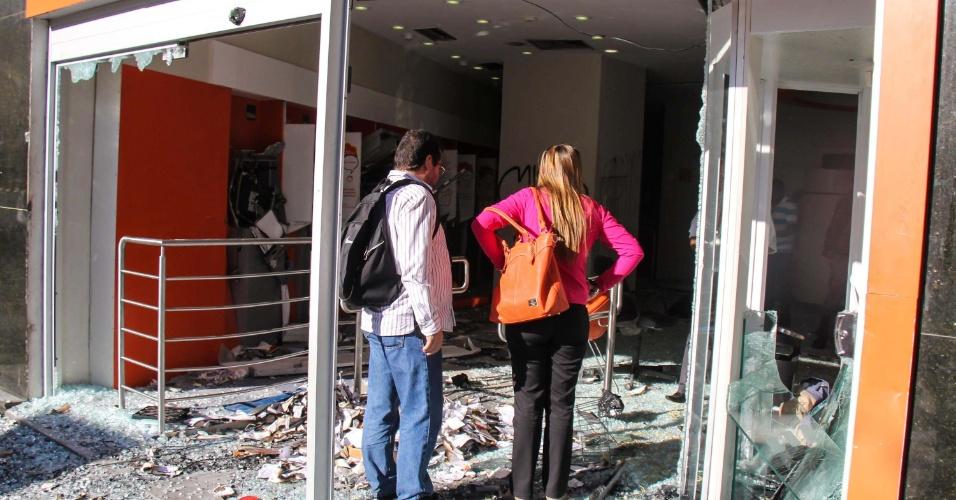 19.jun.2013 - Pedestres observam banco vandalizado na praça Sete, no centro de Belo Horizonte, durante a madrugada desta quarta-feira (19). O segundo dia seguido de protestos na cidade terminou com vandalismo e ação da tropa de choque da Polícia Militar, que chegou por volta das 0h30 ao centro para conter um grupo de manifestantes que quebrou vidraças de lojas e bancos