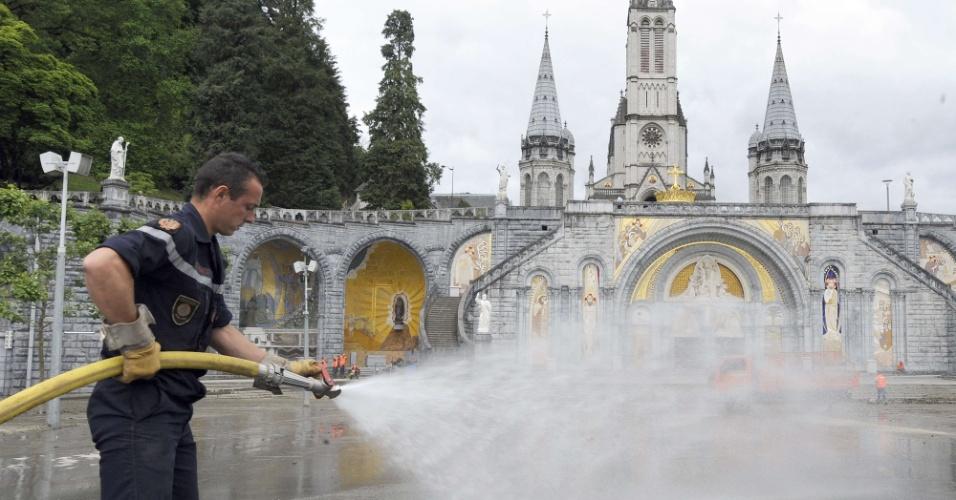 20.jun.2013 - Bombeiro participa da limpeza do santuário de Lourdes, na França, que foi atingido pela enxurrada que inundou a cidade. O local de peregrinação católica pode ficar fechado por meses, devidos aos danos