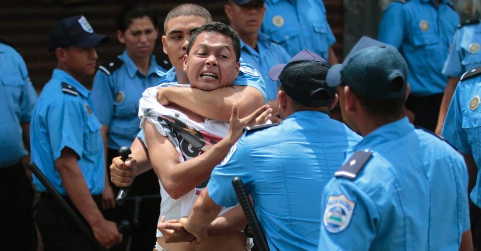 20.jun.2013 - Jovem é detido por policiais em frente ao Instituto de Seguro Social da Nicarágua, em Manágua, durante o quarto dia de protestos contra a reforma da previdência proposta pelo governo. Os aposentados discordam do valor e pedem uma pensão mensal de no mínimo US$ 90 (cerca de R$ 205)