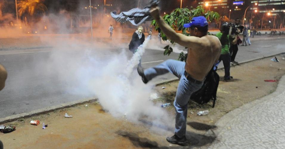 20.jun.2013 - Manifestante chuta bomba de gás lacrimogêneo durante confronto com a polícia no centro do Rio de Janeiro na noite desta quinta-feira