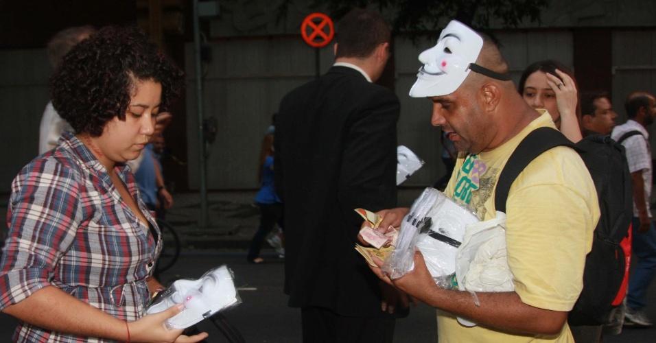 20.jun.2013 - Manifestante compra máscara na igreja da Candelária, no centro do Rio de Janeiro, em protesto nesta quinta-feira (20). Os manifestantes marcham até a Prefeitura do Rio de Janeiro