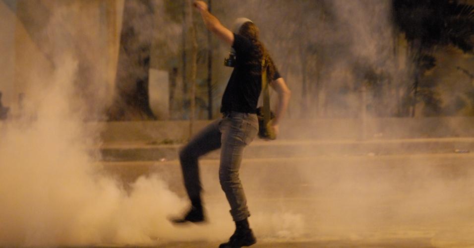 20.jun.2013 - Manifestante se esquiva de bombas de gás lacrimogêneo durante confronto com a polícia no centro do Rio de Janeiro na noite desta quinta-feira
