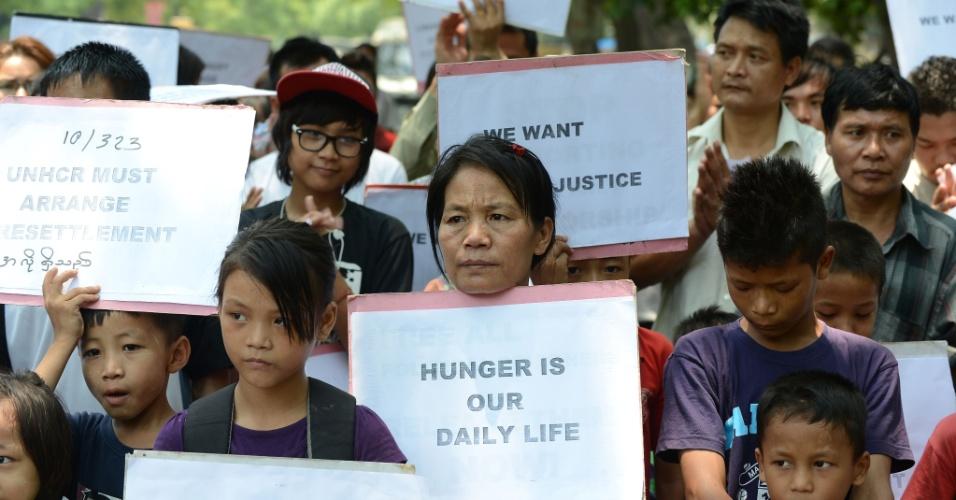 """20.jun.2013 - Manifestantes de Mianmar seguram cartazes nesta quinta-feira (20), Dia Mundial do Refugiado, durante protesto silencioso em Nova Délhi (Índia). Eles pedem ao alto comissário das Nações Unidas que acelere o programa de ajuda aos refugiados de Mianmar. Os cartazes têm os textos """"Fome é nossa vida diária"""", """"Queremos justiça"""" e """"Precisamos de proteção"""""""