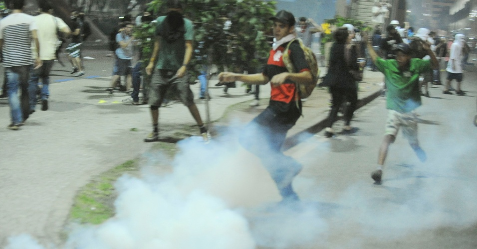 20.jun.2013 - Manifestantes se esquivam de bombas de gás lacrimogêneo durante confronto com a polícia no centro do Rio de Janeiro na noite desta quinta-feira