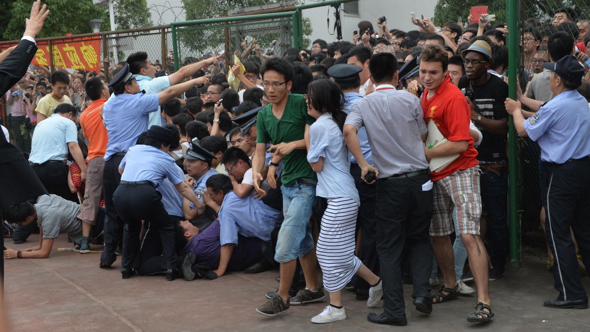 20.jun.2013 - Pessoas caem durante empurra-empurra nesta quinta-feira (20) enquanto tentam ver David Beckam, durante uma visita do ex-jogador de futebol à Universidade de Tonji, em Xangai (China). Ao menos cinco pessoas se feriram, incluindo uma policial, de acordo com a imprensa local e um fotógrafo da AFP que presenciou a cena