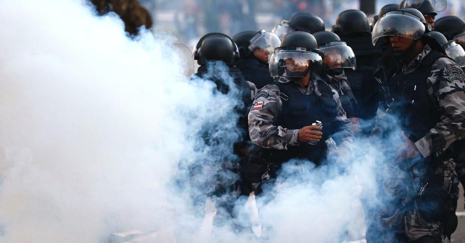 20.jun.2013 - Policiais se protegem de bombas de gás lacrimogêneo durante protesto nas imediações da Arena Fonte Nova, em Salvador. Em apoio às manifestações que ocorrem paralelamente em diversas cidades do Brasil, os manifestantes protestam contra a precariedade dos serviços públicos e contra a corrupção no país