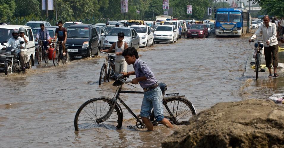 20.jun.2013 - Veículos atravessam nesta quinta-feira (20) via alagada por águas do rio Yamuna em Nova Délhi (Índia), após enchentes que já mataram mais de 160 em duas semanas na Índia e no Nepal. Helicópteros militares entregaram suprimentos de emergência nesta quarta-feira (19) para ajudar pessoas que ficaram ilhadas