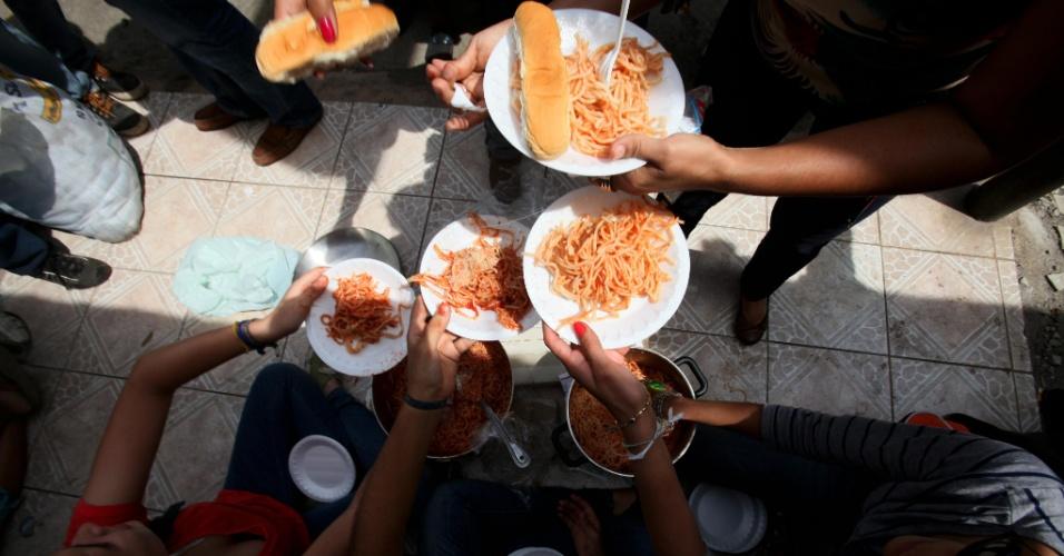 Jovens repartem comida com os mais velhos que participam de um protesto próximo à sede do Instituto Nicaraguense de Segurança Social, em Manágua. Os idosos exigem benefícios do governo