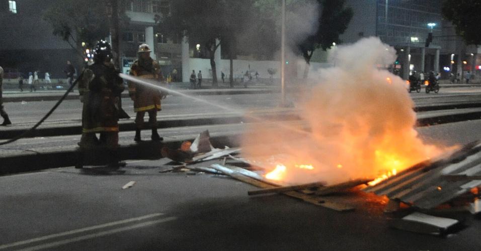20.jun.2013 - Bombeiros apagam fogo causado por protesto no centro do Rio de Janeiro (RJ) na noite desta quinta-feira