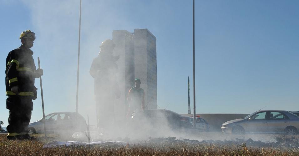 21.jun.2013 - Bombeiros apagam fogo de gramado em frente ao Congresso Nacional, em Brasília, na manhã desta sexta-feira (21). O protesto na cidade foi um dos mais tensos entre os mais de 90 atos organizados pelo país na noite de quinta-feira (20). Após tentarem entrar no Congresso e no Palácio do Planalto, manifestantes depredaram o Palácio do Itamaraty, sede do Ministério das Relações Exteriores