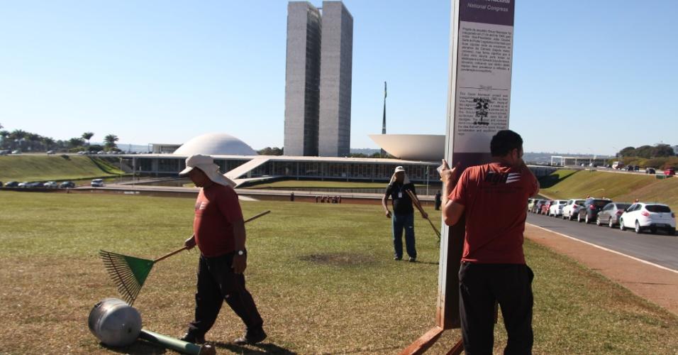 21.jun.2013 - funcionários retiram placa danificada em frente ao Congresso Nacional, em Brasília, na manhã desta sexta-feira (21). O protesto na cidade foi um dos mais tensos entre os mais de 90 atos organizados pelo país na noite de quinta-feira (20). Após tentarem entrar no Congresso e no Palácio do Planalto, manifestantes depredaram o Palácio do Itamaraty, sede do Ministério das Relações Exteriores
