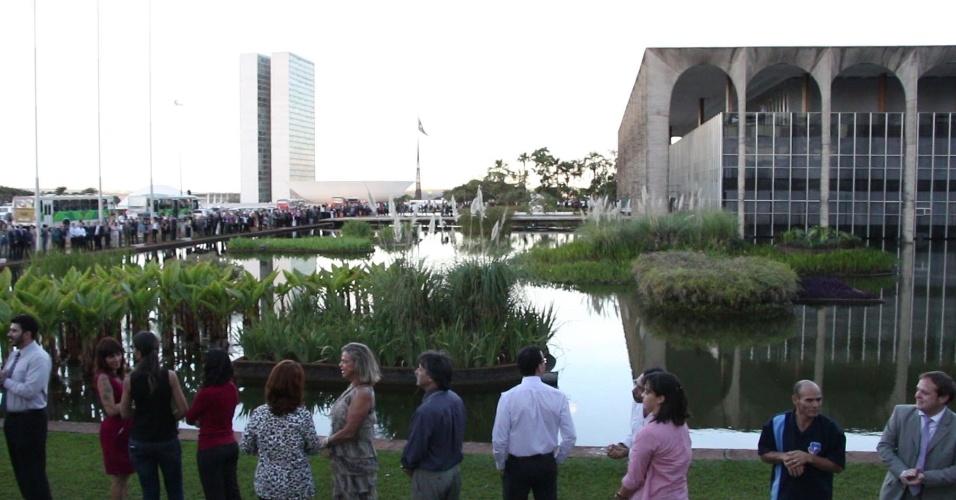 21.jun.2013 - Um dia após a depredação do Palácio do Itamaraty, sede do Ministério das Relações Exteriores, em Brasília, funcionários deram um abraço simbólico no prédio. Ao fundo, o Congresso Nacional