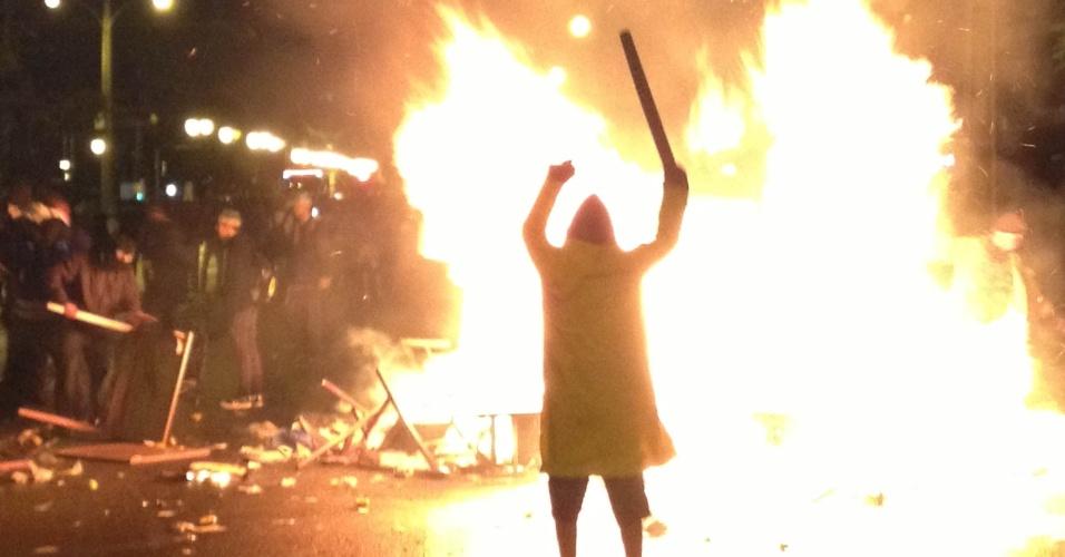 21.jun.2013 - Manifestante observa fogueira feita com mesas e cadeiras saqueadas de lanchonete na avenida Cândido de Abreu, em Curitiba, na madrugada deste sábado (22). A polícia dispersou a multidão com gás lacrimogêneo e balas de borracha