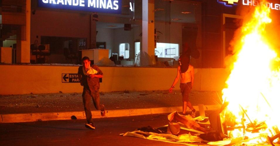 22.jun.2013- Manifestantes depredam patrimônio público e privado após confronto com policiais militares em Belo Horizonte, neste sábado, nas proximidades do estádio Mineirão. Uma fogueira foi feita com objetos tirados das lojas
