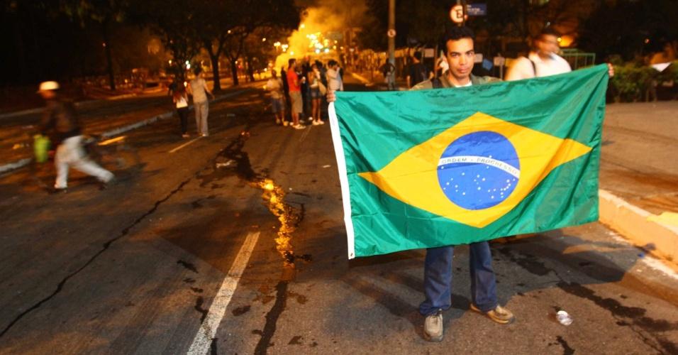 Homem segura bandeira do Brasil durante protesto em Belo Horizonte