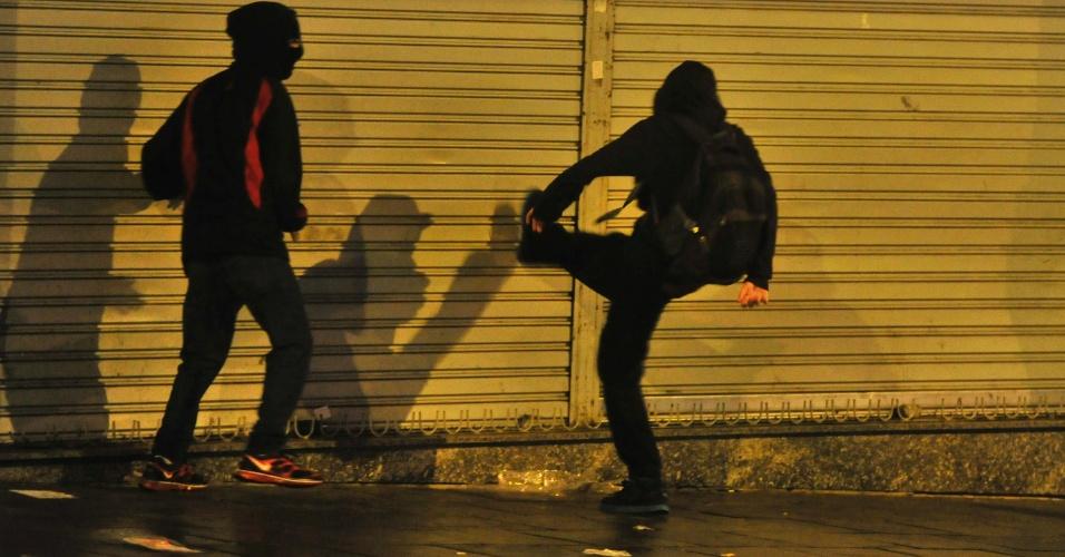 24.jun.2013 - Manifestante chuta porta de loja durante protesto em Porto Alegre, na noite desta segunda-feira (24). A cavalaria da Brigada Militar dispersou manifestantes e prendeu 15 vândalos