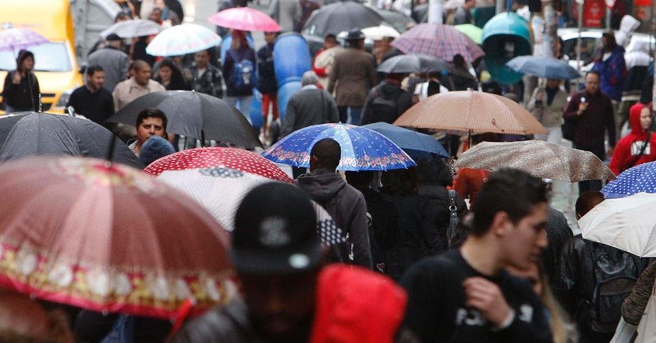 24.jun.2013 - Pedestres enfrentam chuva no centro de Porto Alegre, na tarde desta segunda-feira (24)