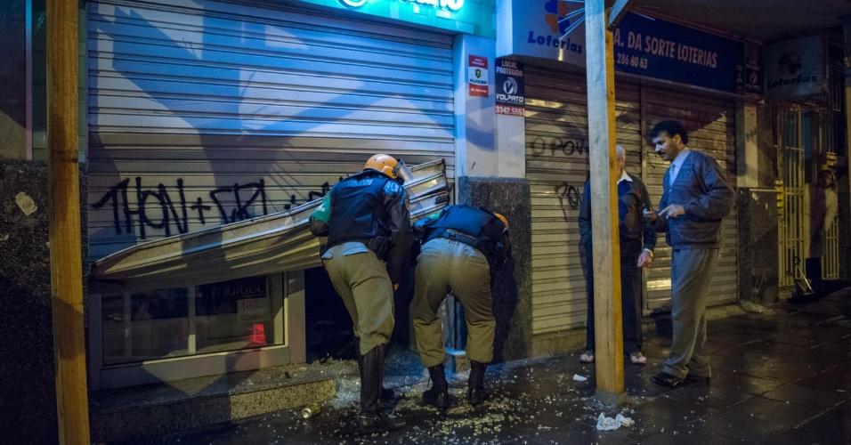 24.jun.2013 - Porta de loja fica depredada após protesto em Porto Alegre, na noite desta segunda-feira (24). A cavalaria da Brigada Militar dispersou manifestantes e prendeu 15 vândalos