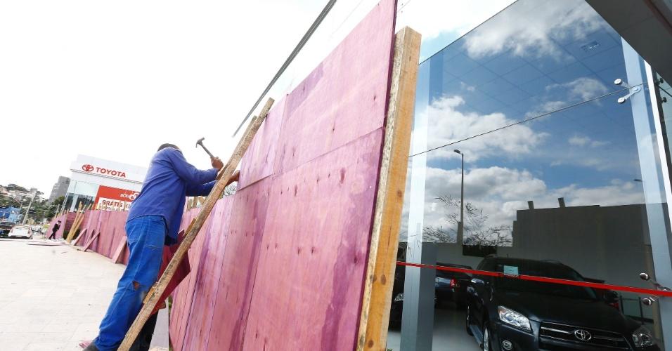 25.jun.2013 - Concessionárias de veículos cobriram vidraças com tapumes na avenida Antônio Carlos, em Belo Horizonte, para proteger de possíveis depredações durante protestos