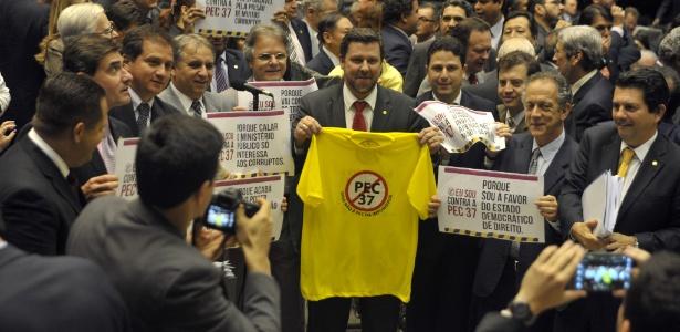 Deputados da bancada do PSDB mostram cartazes contrários à PEC 37 em sessão de votação nesta terça-feira (25), em Brasília