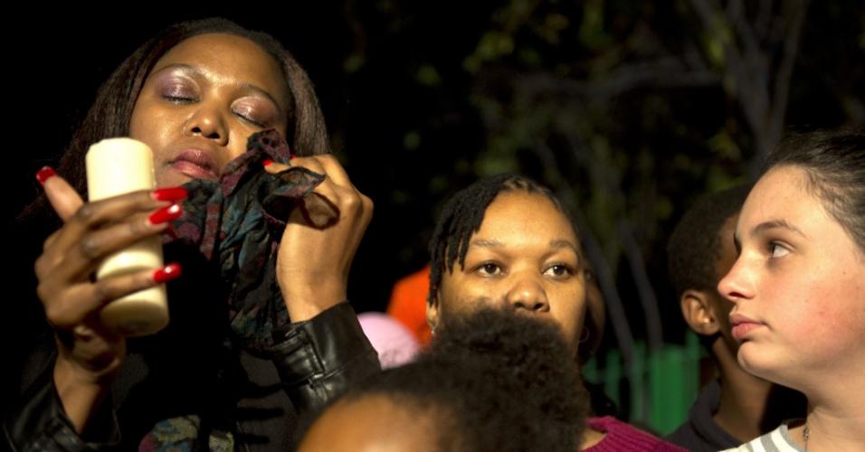 25.jun.2013 - Mulher limpa lágrimas e segura vela durante uma vigília do lado de fora do Hospital do Coração Mediclinic em Pretória, onde o ex-presidente da África do Sul Nelson Mandela está internado em estado crítico. O grupo orou e cantou canções religiosas em apoio a Mandela