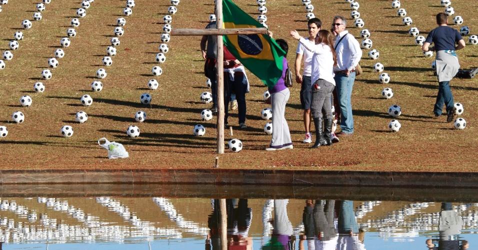 """26.jun.2013 - Manifestantes da ONG """"Rio de Paz"""" espalham bolas de futebol marcadas com uma cruz vermelha em frente ao Congresso Nacional, em Brasília, na manhã desta quarta-feira (26)"""