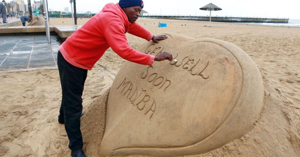 27.jun.2013 - Artista dá toques finais em escultura de areia construída em homenagem a Nelson Mandela em uma praia de Durban, na África do Sul. A família de Mandela confirmou, nesta quinta-feira (27), que o estado de saúde do ganhador do Nobel da paz é muito crítico