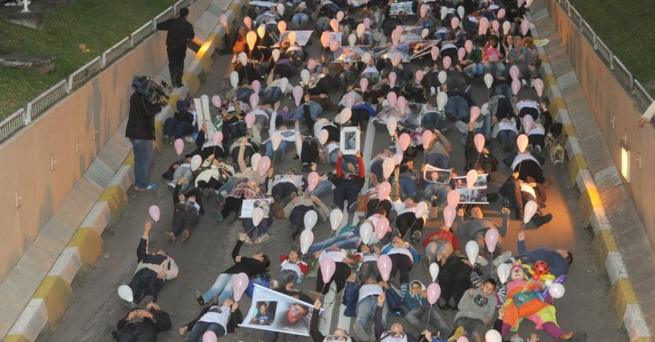 27.jun.2013 - Centenas de pessoas participaram de uma homenagem às 242 vítimas do incêndio na boate Kiss em Santa Maria. Deitado no chão, o grupo soltou balões brancos em uma das principais vias da cidade. A tragédia completa cinco meses nesta quinta-feira