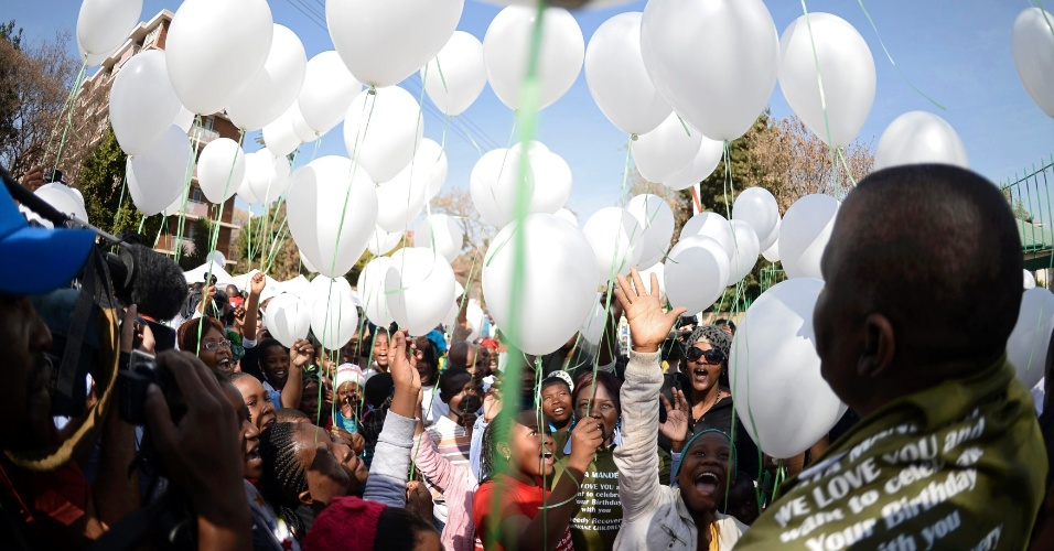 27.jun.2013 - Crianças soltam 95 balões brancos para lembrar o próximo aniversário de Nelson Mandela, em 18 de julho, na frente do hospital onde o ex-presidente da África do Sul está internado, em  Pretoria