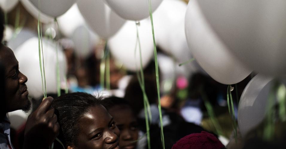 27.jun.2013 - Grupo leva balões brancos ao hospital onde está internado Nelson Mandela, que piorou de estado de saúde nos últimos dias, em Pretoria, na África do Sul