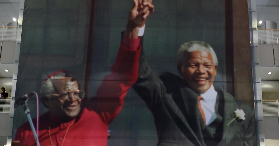 27.jun.2013 - Pessoas passam diante de uma foto de Nelson Mandela com o arcebispo Desmond Tutu na prefeitura da Cidade do Cabo, na África do Sul