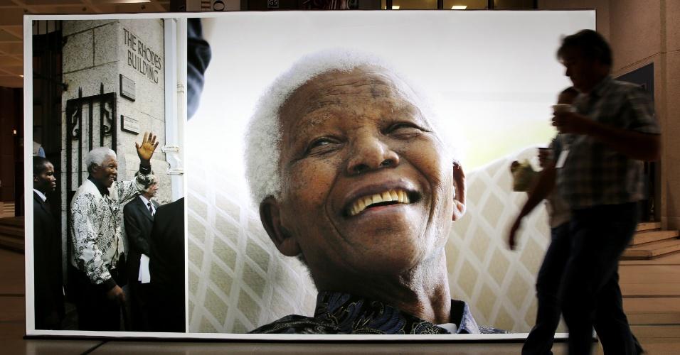 27.jun.2013 - Pessoas passam diante de uma foto de Nelson Mandela na prefeitura da Cidade do Cabo, na África do Sul