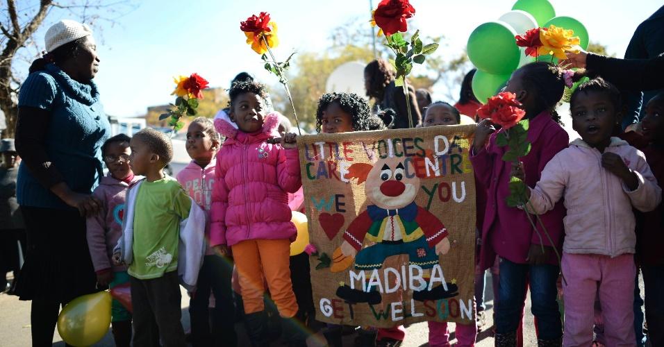 28.jun.2013 - Crianças seguram cartaz com mensagem de apoio para o ex-presidente sul-africano Nelson Mandela, nesta sexta-feira (28), em frente ao Hospital do Coração Mediclinic, em Pretória, onde ele está internado