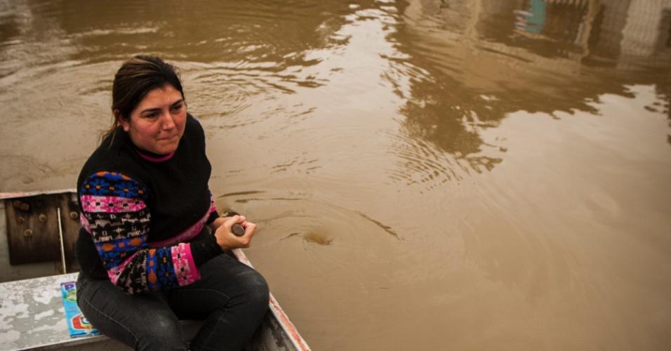 1º.jul.2013 - Moradora do bairro Navegantes, na cidade de União da Vitória (PR), passam por área alagada após as fortes chuvas que atingem a região. Foi decretado estado de emergência em 59 municípios do Estado