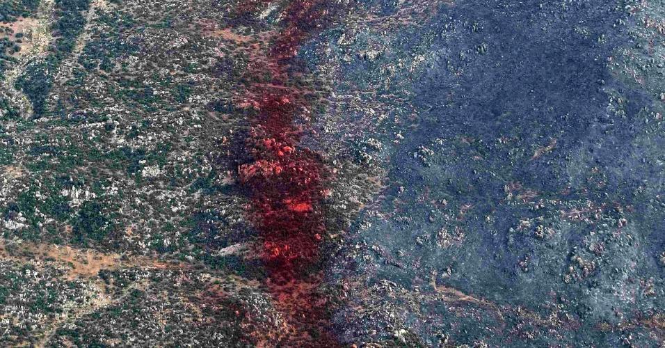2.jul.2013 - Em imagem aérea desta segunda-feira (1), divulgada nesta terça (2), mancha vermelha de produto químico anti-chamas separa a área queimada de floresta no Estado de Arizona (EUA) da parte intacta, à esquerda. 19 bombeiros morreram combatendo o incêndio, na maior tragédia do tipo em 80 anos. Eles teriam sido engolidos rapidamente pelo fogo, sem tempo de se proteger em abrigos semelhantes a casulos