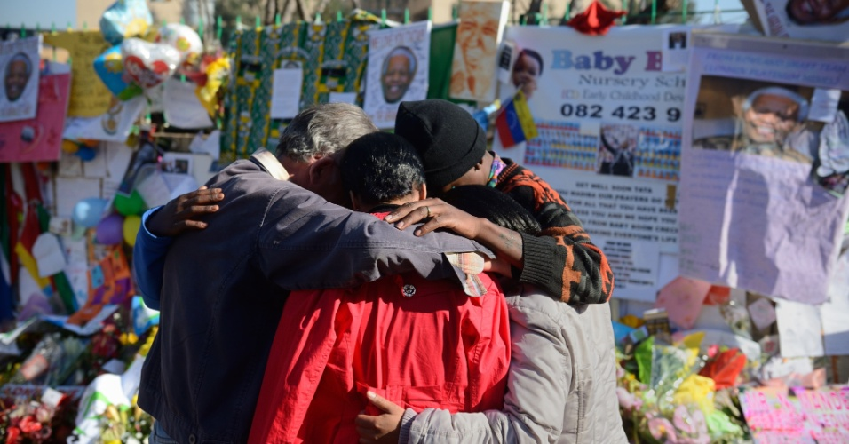 2.jul.2013 - Família se abraça em frente a mural com mensagem e flores colocadas em homenagem a Nelson Mandela em frente ao hospital onde o ex-presidente sul-africano está hospitalizado, em Pretória. Mandela, que completará 95 anos em 18 de julho, está em estado crítico, mas estável