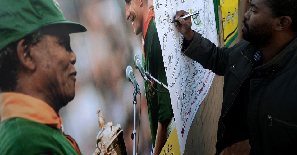 2.jul.2013 - Homem escreve mensagem em mural em homenagem a Nelson Mandela em frente ao hospital onde o ex-presidente sul-africano está hospitalizado, em Pretória. Mandela, que completará 95 anos em 18 de julho, está em estado crítico, mas estável