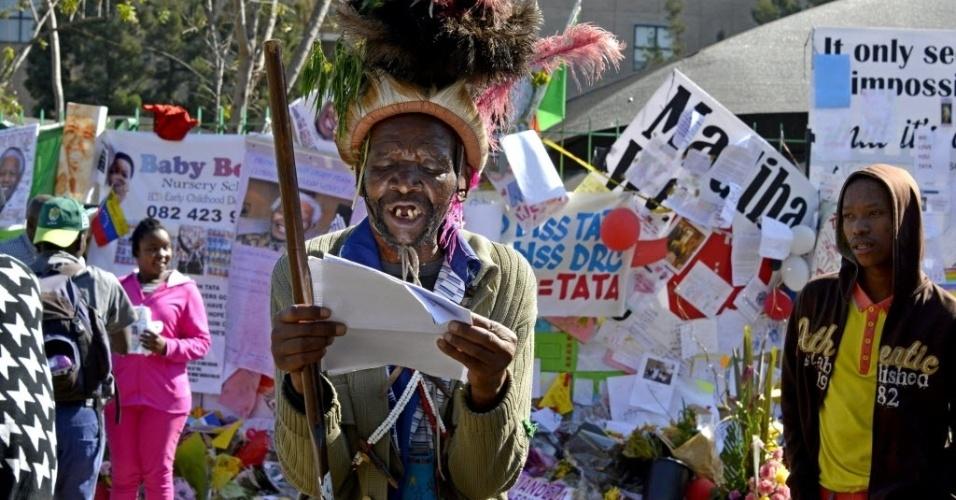 2.jul.2013 - Homem lê sermão do lado de fora do hospital do coração Mediclinic, em Pretória, nesta terça-feira (2), onde o ex-presidente da África do Sul Nelson Mandela está internado