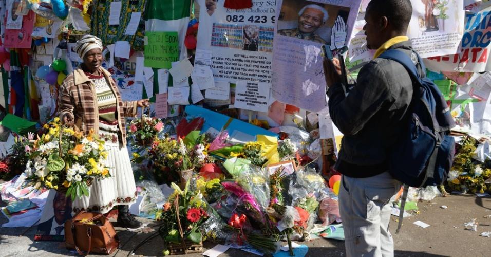 3.jul.2013 - Mulher tira foto em frente às mensagens em homenagem ao ex-presidente Nelson Mandela do lado de fora do Hospital do Coração Mediclinic, em Pretória, África do Sul. Mandela está internado no local há três semanas por causa de uma doença pulmonar